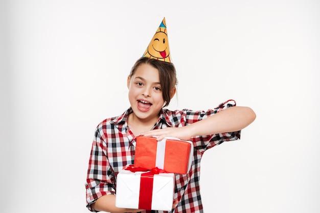 Szczęśliwa młoda urodzinowa dziewczyna pozuje z prezentami