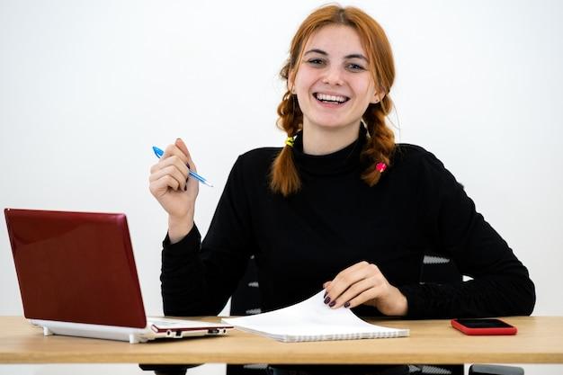 Szczęśliwa młoda urzędniczka kobieta siedzi za pracującym biurkiem z laptopem, telefonem komórkowym i notatnikiem.