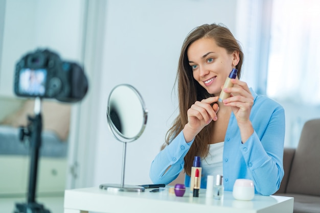 Szczęśliwa młoda uśmiechnięta kobieta blogger influencer trzyma podstawę podczas nagrywania jej piękna blogu o makijażu i kosmetykach w domu. blogowanie i wpływanie na odbiorców