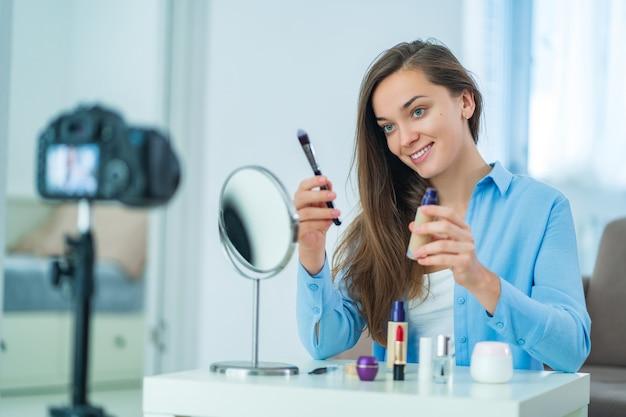 Szczęśliwa młoda uśmiechnięta kobieta blogger wideo influencer gospodarstwa pędzla i podstawy podczas nagrywania jej blog piękności na temat makijażu i kosmetyków w domu. blogowanie i wpływanie na odbiorców