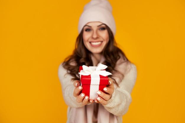 Szczęśliwa młoda uśmiechnięta kobieta trzyma czerwone pudełko z przodu i trzyma, oferując i dając prezenty świąteczne. dziewczyna w swetrze wygląda i daje prezent.
