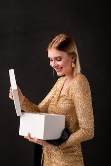 Szczęśliwa młoda uśmiechnięta kobieta w eleganckiej sukience zdejmując pokrywę z pudełka i patrząc na prezent urodzinowy od jej przyjaciół lub chłopaka
