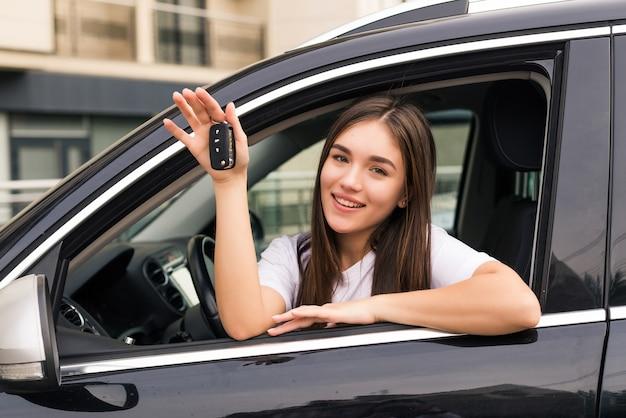 Szczęśliwa młoda uśmiechnięta kobieta z nowym kluczykiem do samochodu