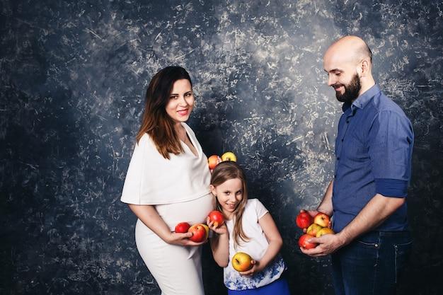 Szczęśliwa młoda wegańska rodzina. ciężarna mama, brodaty ojciec i córeczka trzymają jabłka w rękach i się uśmiechają. dzień jabłka