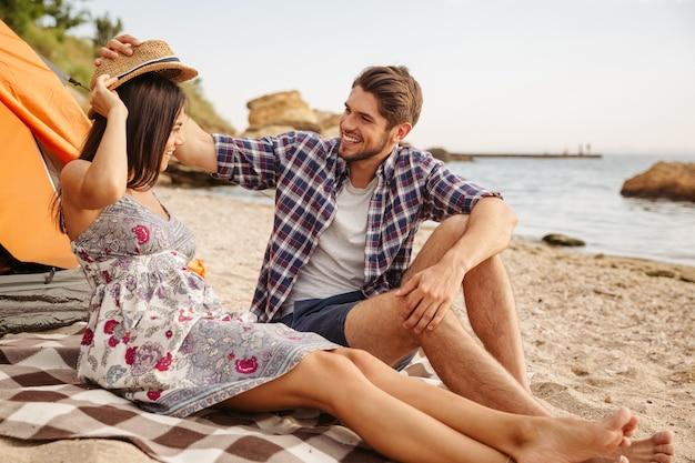 Szczęśliwa młoda wesoła para bawi się na kempingu na plaży