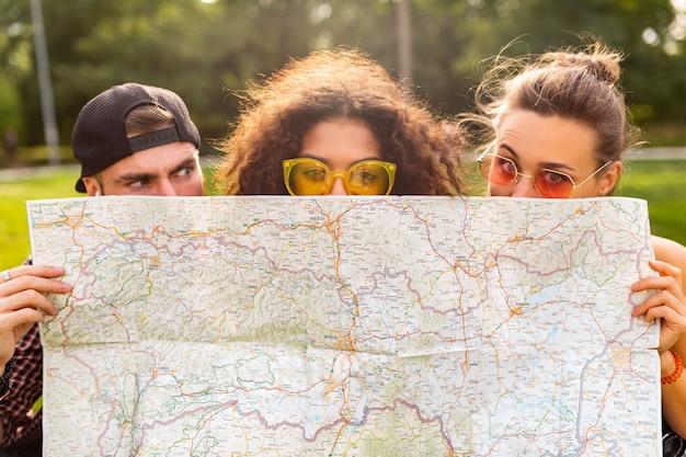Szczęśliwa młoda zabawna firma przyjaciół turystów chowających się za mapą w okularach przeciwsłonecznych, mężczyzna i kobiety, wspólna zabawa, podróże