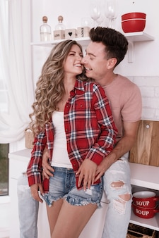 Szczęśliwa młoda zakochana para ściska się i bawi się w kuchni w walentynki rano. stylowy mężczyzna i kobieta z długimi włosami relaks w domu