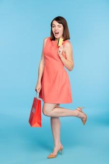 Szczęśliwa młoda zalotna kobieta w czerwonej sukience mrugając, pokazując kartę bankową po wizycie w centrum handlowym w sezonowej wyprzedaży
