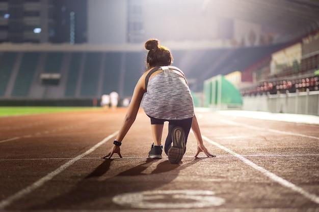 Szczęśliwa młoda żeńska atleta ustawiająca na zaczyna pozyci w stadium