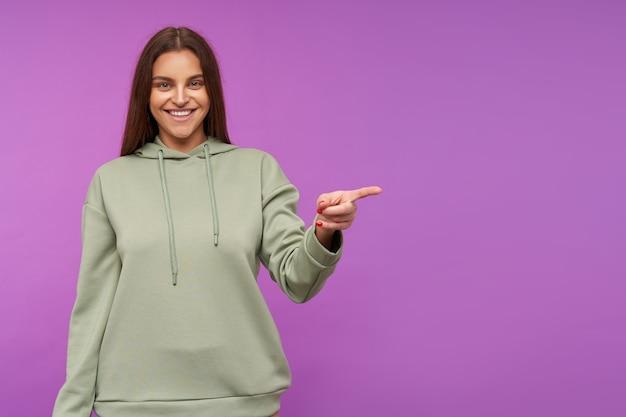 Szczęśliwa młoda zielonooka brunetka kobieta z naturalnym makijażem uśmiecha się szeroko, pokazując na bok z podniesioną ręką, będąc w dobrym nastroju, pozując na fioletowej ścianie