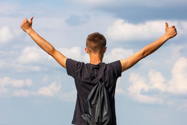 Szczęśliwa młody człowiek pozycja na wierzchołku z jego rękami up