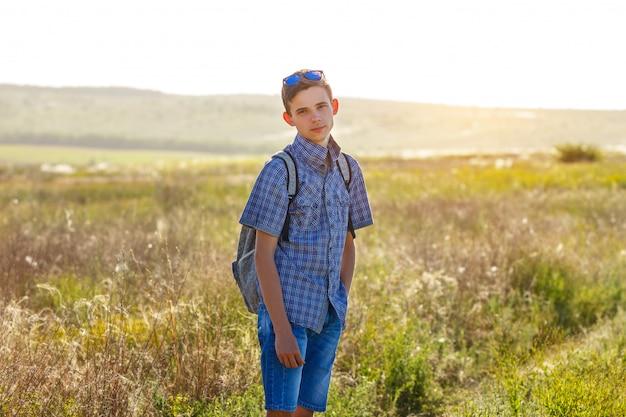 Szczęśliwa młody człowiek pozycja z plecakiem outdoors na słonecznym dniu.