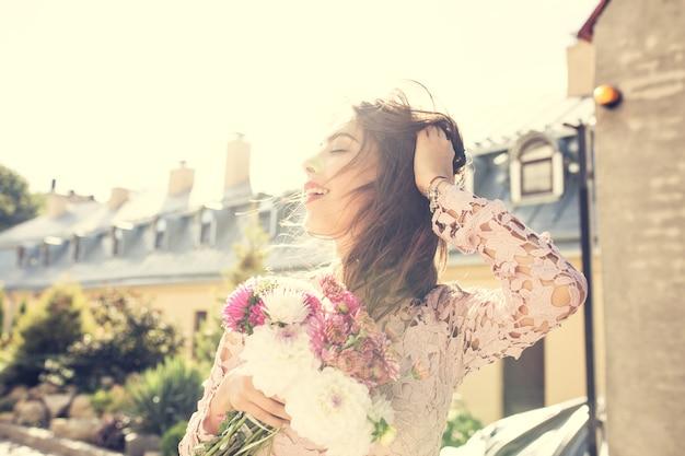 Szczęśliwa modelka brunetka w różowej sukience z kwiatami w ręce na tle miasta. efekt tonowania w stylu vintage