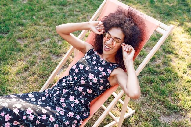 Szczęśliwa modna czarna kobieta ze stylową kręconą fryzurą siedzi na szezlongu na niesamowitym zielonym trawniku