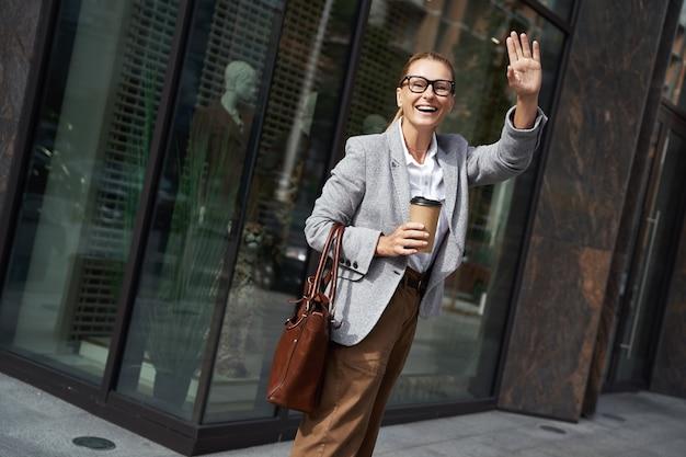 Szczęśliwa modna kobieta trzymająca filiżankę kawy i machająca do kogoś, stojąc w