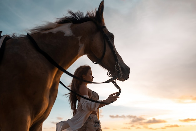 Szczęśliwa modna młoda kobieta pozuje z koniem na plaży