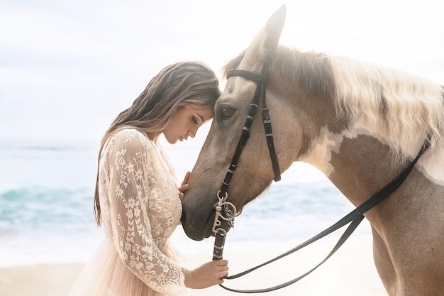 Szczęśliwa modna młoda kobieta w białej sukni pozuje z koniem na plaży.