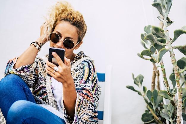 Szczęśliwa modna moda młoda piękna kobieta używa nowoczesnego telefonu technologicznego, aby dzwonić do przyjaciół