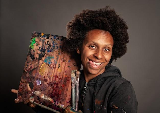 Szczęśliwa murzynka trzyma paletę i paintbrushes