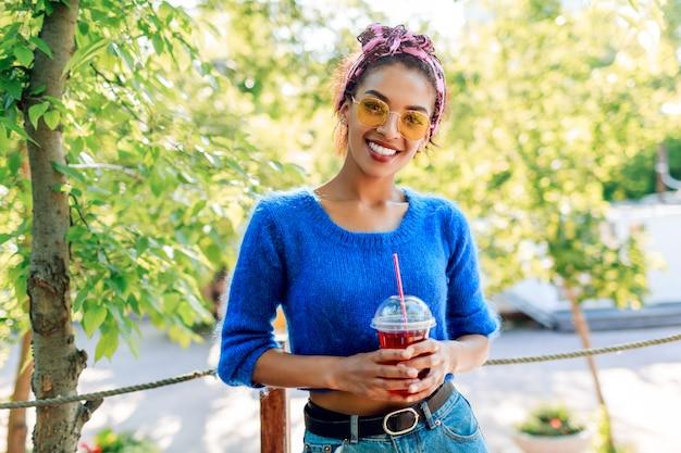 Szczęśliwa murzynka ze stylową fryzurą z opaską spędza weekend w parku, spacerując i pijąc lemoniadę.