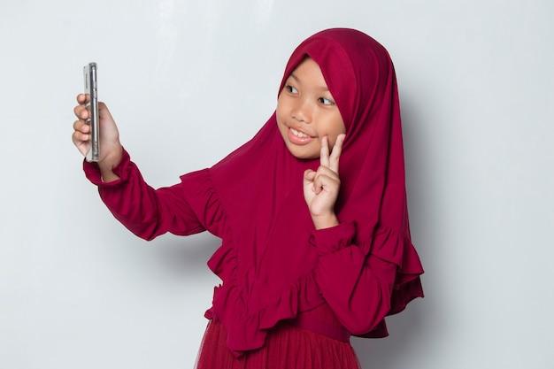 Szczęśliwa muzułmańska azjatycka dziewczynka używająca smartfona selfie na białym tle