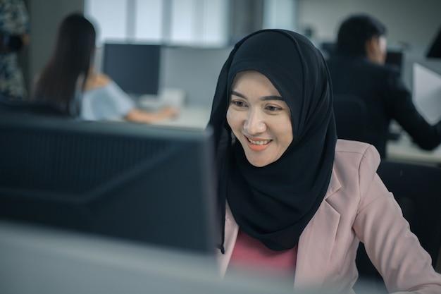 Szczęśliwa muzułmańska azjatycka kobieta pracująca i korzystająca z komputera na spotkaniu biurowym