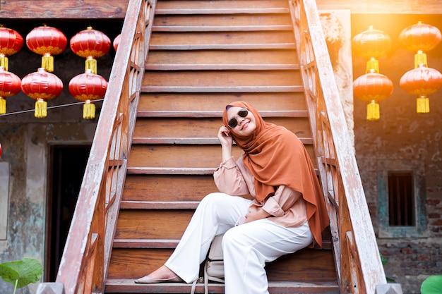 Szczęśliwa muzułmańska kobieta turystyczna siedząca na schody w chińskiej domowej atmosferze, azjatycka kobieta w wakacje. koncepcja podróży. motyw chiński.