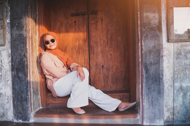 Szczęśliwa muzułmańska kobieta turystyczna siedzi na drzwiach w chińskiej domowej atmosferze, azjatycka kobieta w wakacje. koncepcja podróży. motyw chiński.
