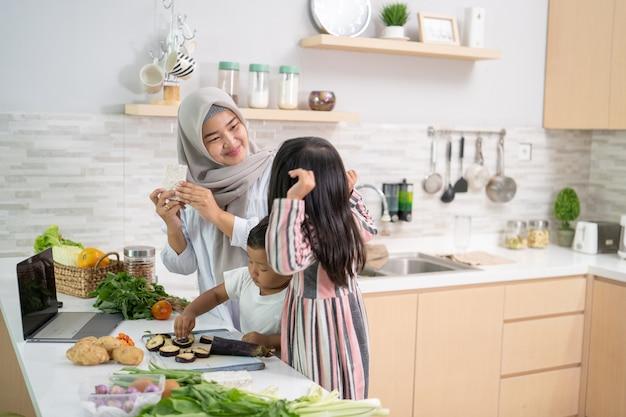Szczęśliwa muzułmańska matka i jej dzieci gotują i bawią się razem w domu przygotowując się do kolacji iftar