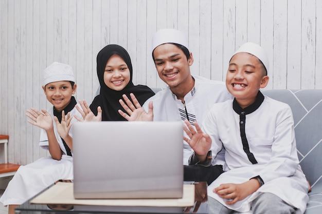 Szczęśliwa muzułmańska rodzina prowadząca rozmowę wideo przed laptopem z gestem przywitania lub powitania ręcznie podczas uroczystości eid mubarak