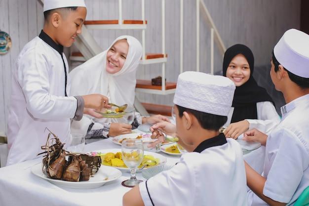Szczęśliwa muzułmańska rodzina świętująca eid mubarak ze wspólnym jedzeniem w jadalni