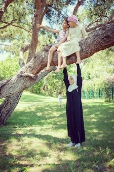 Szczęśliwa muzułmańska rodzina w drzewo parku