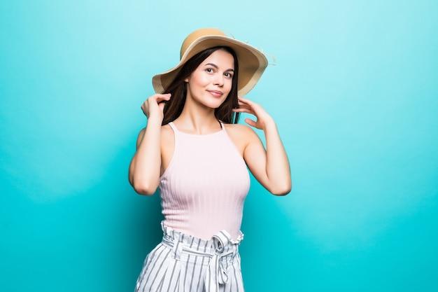 Szczęśliwa myśląca młoda kobieta, patrząc w słomkowy kapelusz na niebieskiej ścianie.