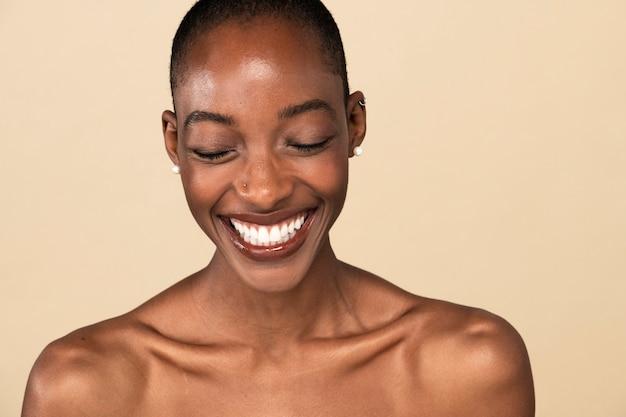 Szczęśliwa naga czarna kobieta na beżowym tle