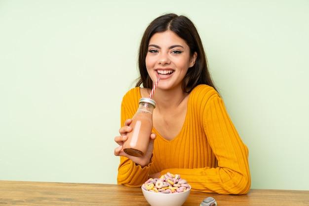 Szczęśliwa nastolatek dziewczyna ma śniadanie z pucharem zboża