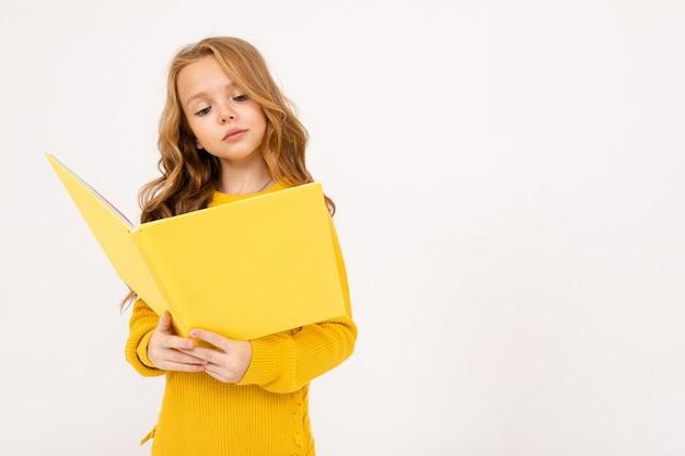 Szczęśliwa nastolatek dziewczyna z czerwonym włosy, kapturzastymi i żółtymi spodniami, czyta dużą żółtą książkę odizolowywającą na bielu
