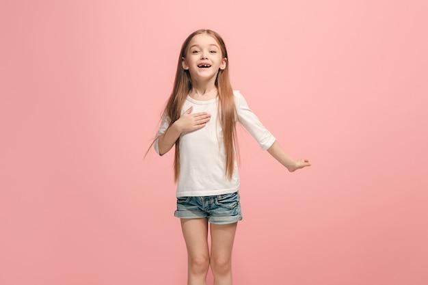 Szczęśliwa nastolatka stojąca i uśmiechająca się przy różowej ścianie