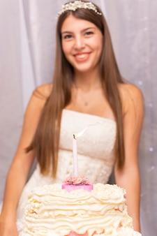 Szczęśliwa nastolatka świętuje swoje piętnaste urodziny ciastem