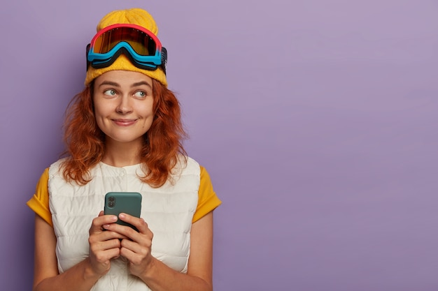 Szczęśliwa nastolatka trzyma nowoczesny telefon komórkowy, nosi maskę snowboardową, na białym tle na fioletowej ścianie.
