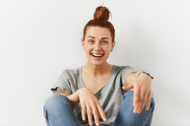 Szczęśliwa nastolatka ubrana w rude włosy w kok, relaks w domu, siedząc na podłodze, odchylając się do tyłu na białej ścianie, mając beztroski, wesoły wygląd. dość młoda kobieta w ubranie odpoczynku w pomieszczeniu