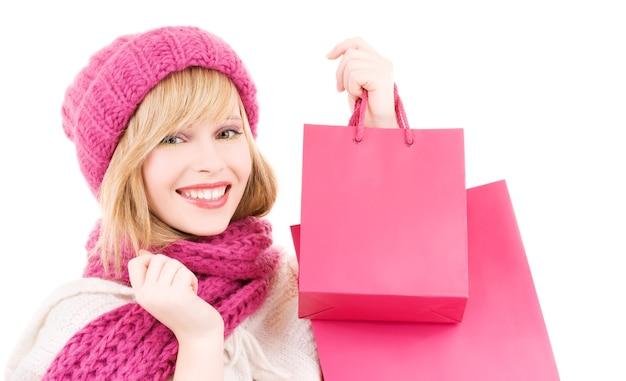 Szczęśliwa nastolatka w kapeluszu z różowymi torbami na zakupy