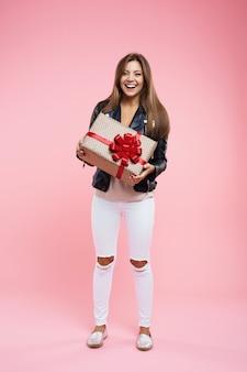 Szczęśliwa nastolatka w podstawowym wyglądzie trzyma prezent urodzinowy