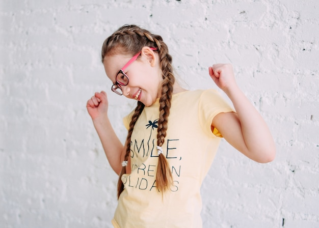 Szczęśliwa nastolatków dziewczyna w żółtej koszulce na białym tle ściana