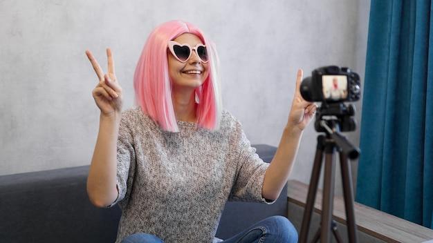Szczęśliwa nastoletnia blogerka z uśmiechniętą twarzą w różowej peruce i okularach. pokazuje znak zwycięstwa, patrząc na kamerę nagrywającą vlog na żywo