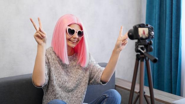 Szczęśliwa nastoletnia blogerka z uśmiechniętą twarzą w różowych perukach i okularach. pokazuje znak zwycięstwa, patrząc na kamerę nagrywającą vlog na żywo, wykonującą wideokonferencję