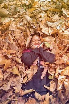 Szczęśliwa nastoletnia dziewczyna ono uśmiecha się w czarnej sukni kłaść w jesieni suchy liść.