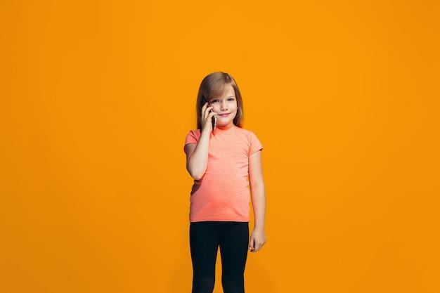 Szczęśliwa nastoletnia dziewczyna stoi i ono uśmiecha się przeciw pomarańcze przestrzeni.