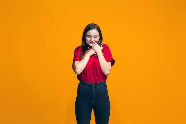 Szczęśliwa nastoletnia dziewczyna stoi i ono uśmiecha się przeciw pomarańcze ścianie