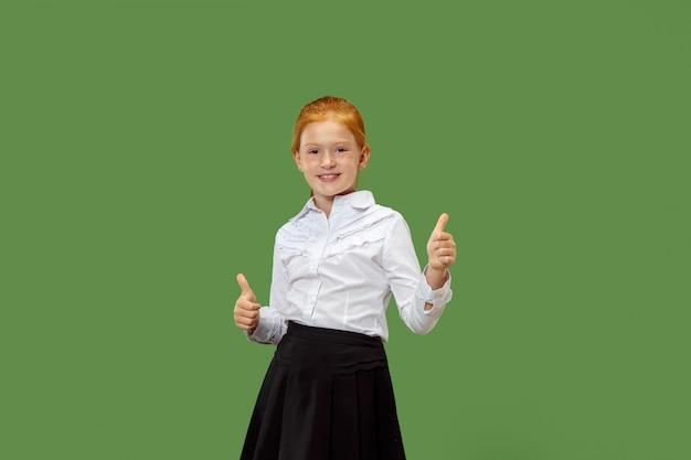 Szczęśliwa nastoletnia dziewczyna stoi i ono uśmiecha się przeciw zieleni