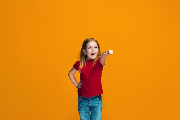 Szczęśliwa nastoletnia dziewczyna wskazuje ciebie, przyrodni długości zbliżenia portret